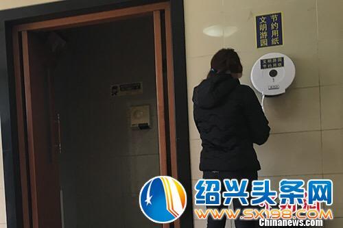 """""""节约用纸""""的标识不仅贴在墙上,也贴在了取纸器上.汤琪 摄-北京"""